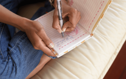 close up of woman sitting crossed legged writing in journal