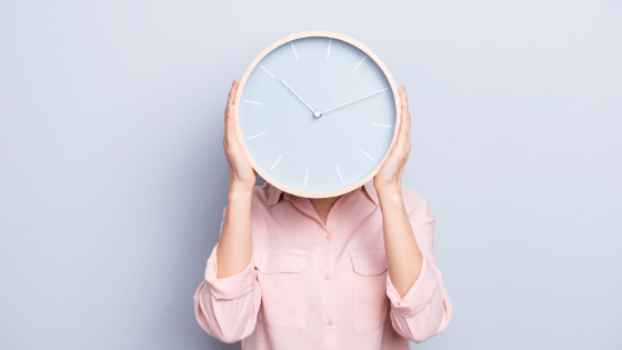 Lady in pink shirt holding a clock that obscures her face